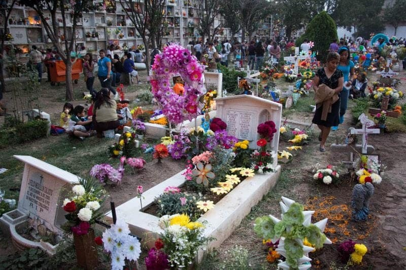 decorating the graves of loved ones for the Day of the Dead in Mexico