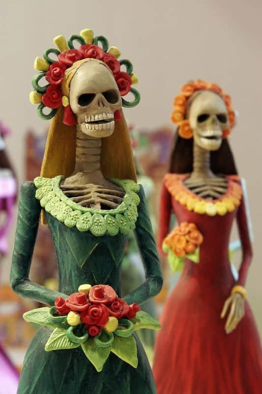 catrinas in papier mache calaveras dressed for celebrations