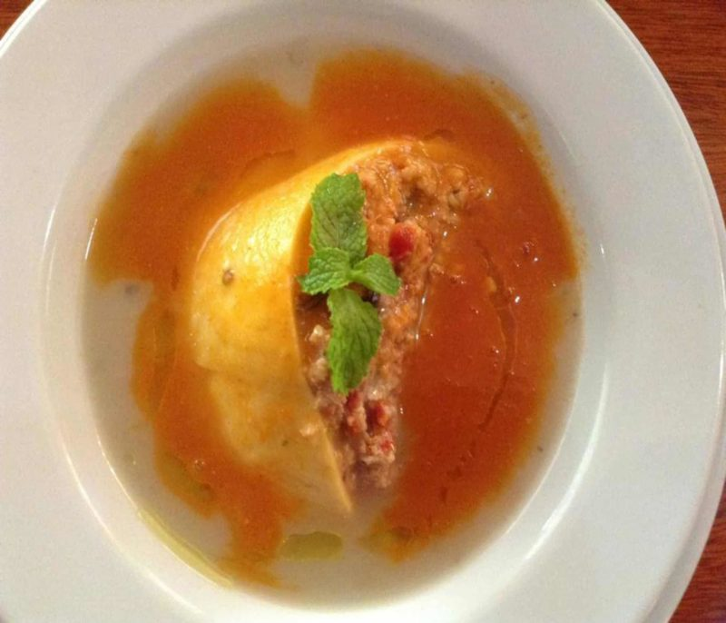 Queso Relleno a rind of cheese stuffed with meat and spices with a light tomato broth.