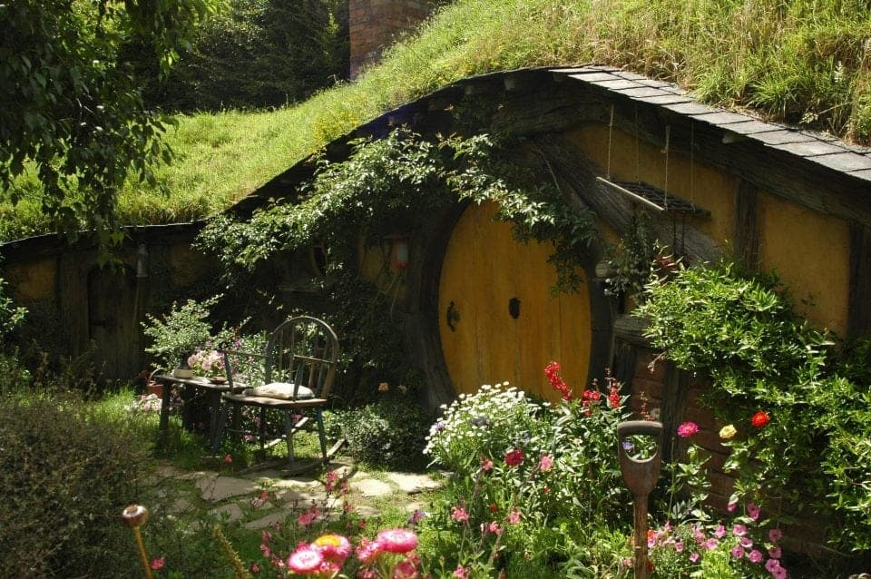 a beautiful fairy garden in Ireland a tiny little house with a moss covered roof and lots of flowers