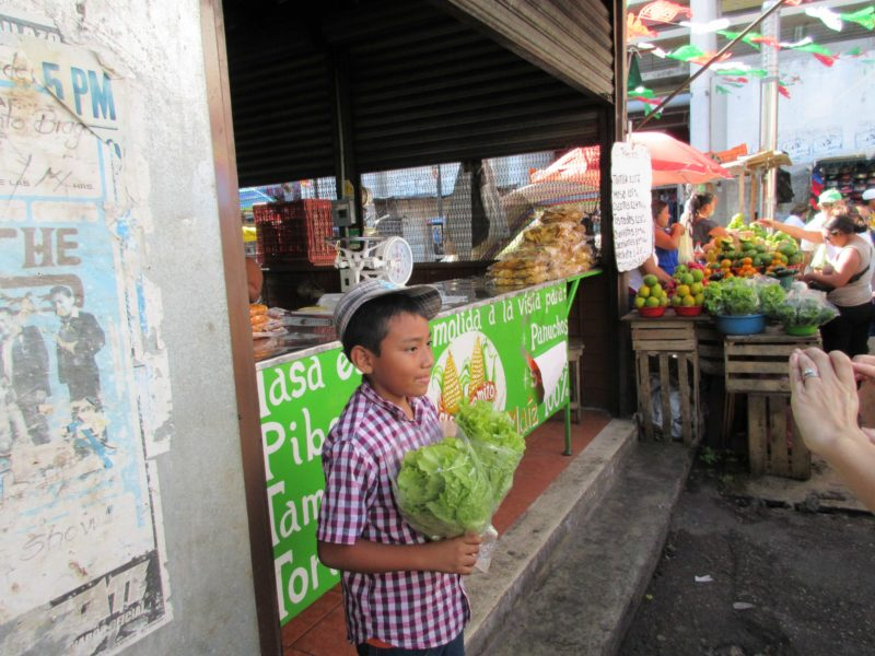 boy selling lettuce at the Lucas Galvez Market in Merida