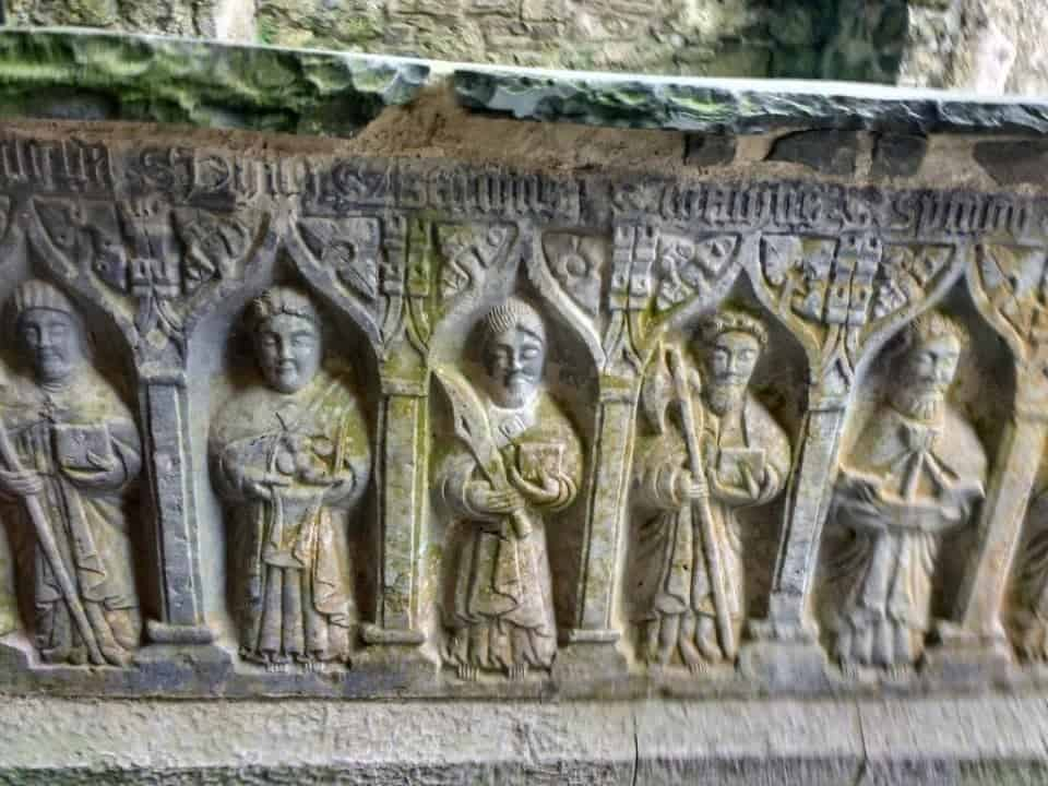 an ancient carved burial crypt with figures on the side as seen at the Rock of Cashel