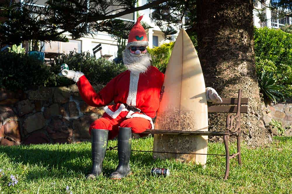An Australian santa sitting on a bench holding a surf board in the bright sunshine