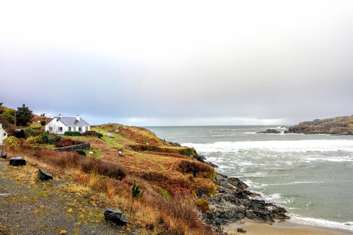 Green Bay Beach in Glencolmcille with a house perched high on the hills surrounding the bay