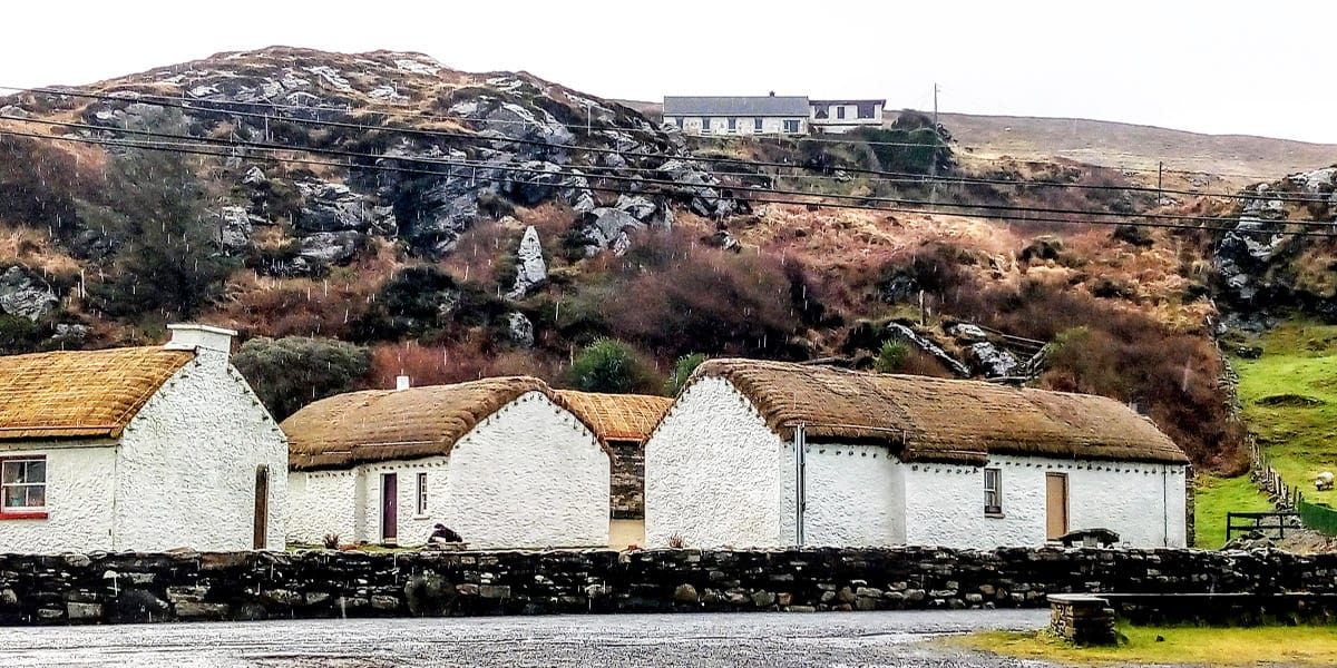 a row of cottages at the Glencolmcille Folk Village showing how the thatch is attached