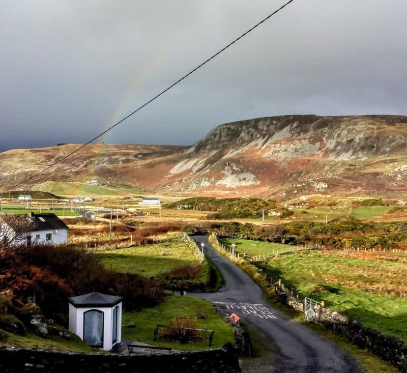 view of the hills of Glencolmcille in Donegal Ireland with a rainbow over the hills