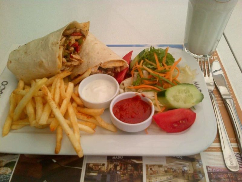 a plate full of beautiful Turkish food a falafel wrap and chips and various dips