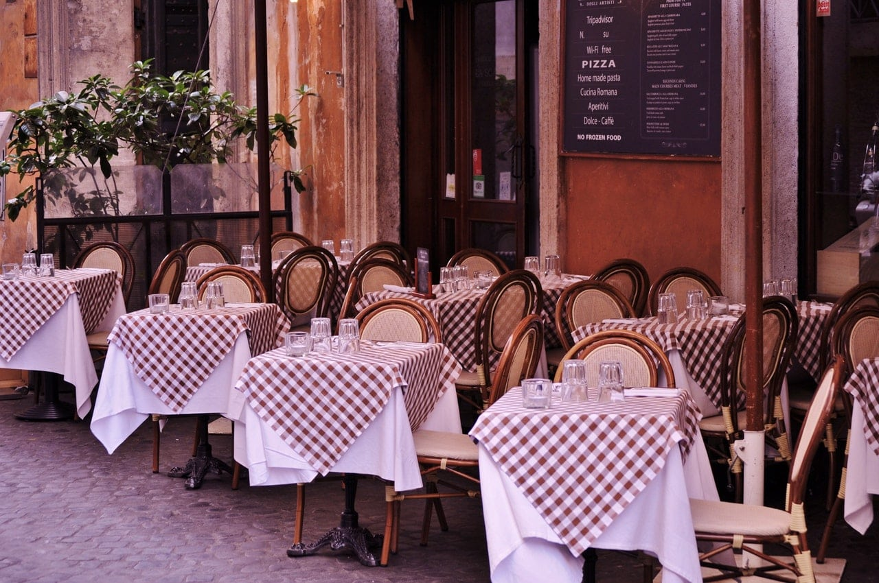 All the best places to eat in Rome view of a Roman restaurant with checked tablecloths al fresco