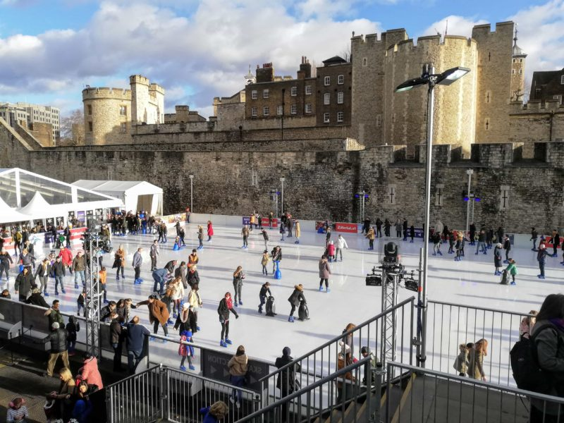 Tower of London skating rink in front of the Tower with hundreds of skaters on the ice.