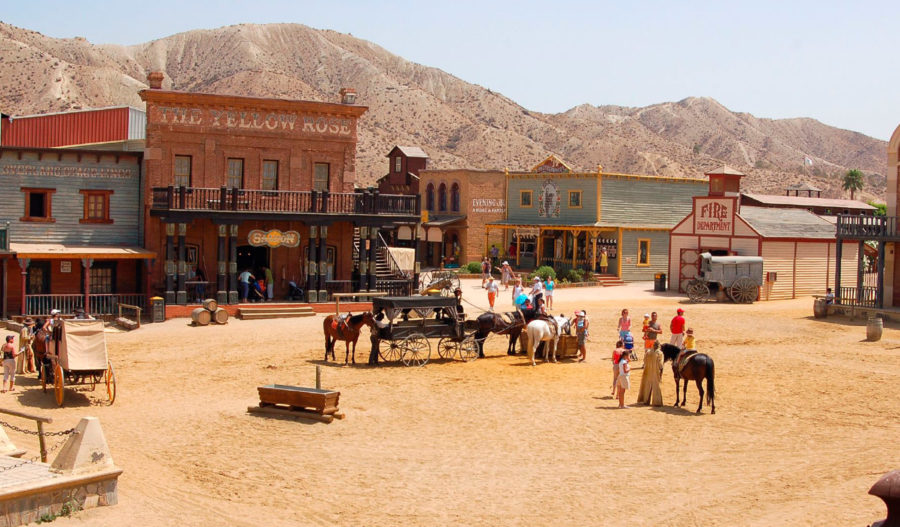 cowboy town in the desert with horses storefronts saloon and gunfighers