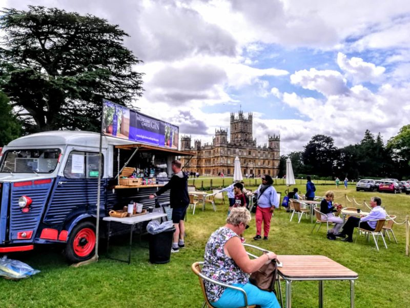 an antique ambulance selling Highclere gin outside of Highclere Castle