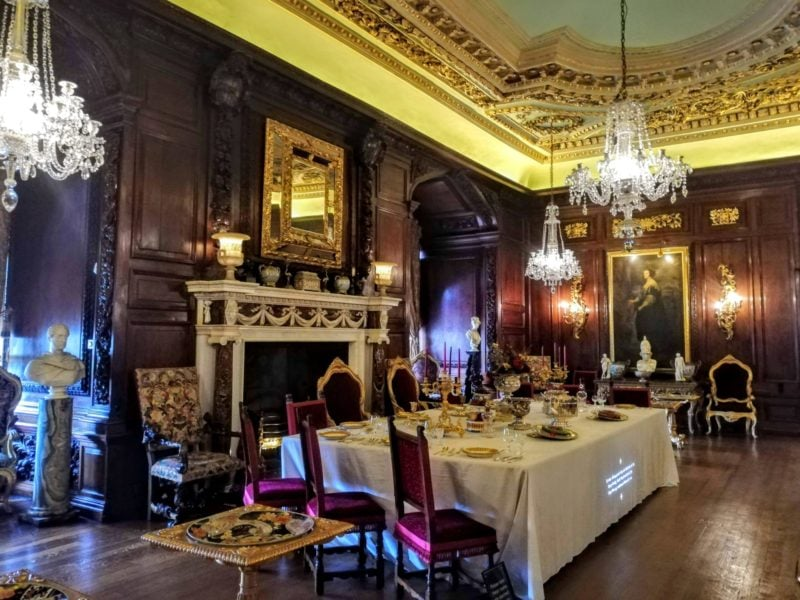 State Rooms at Warwick Castle with ornately gilded ceilings and table set for dinner