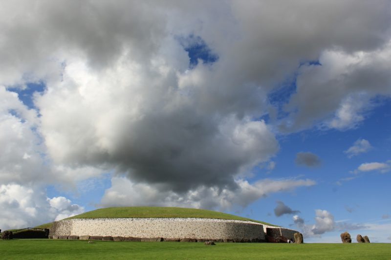 Newgrange under a fluffy cloudy sky buy an Irish heritage card