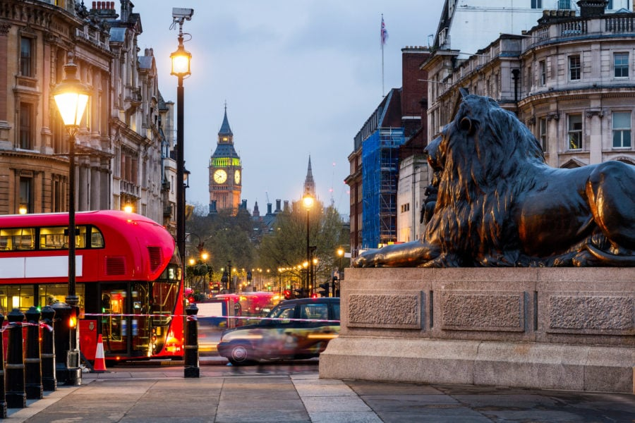 Trafalgar Square Lions with London buses and Big Ben in the background