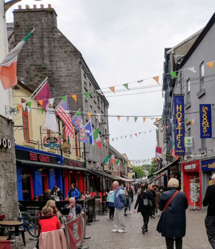 Shop Street Galway city full of people, flags and busers