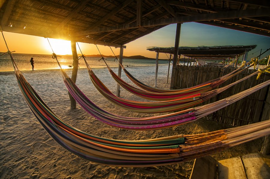 hammocks on the beach of Mexico as the sunsets across the waters