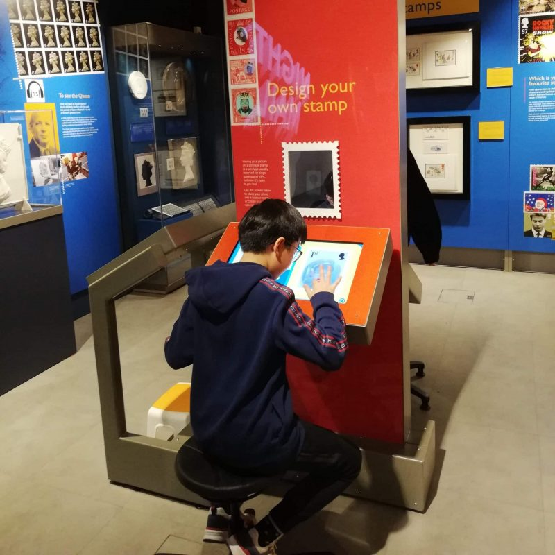 Designing your own stamp at the London Royal Mail Museum a boy sits at a desk in the museum designing his own stamp