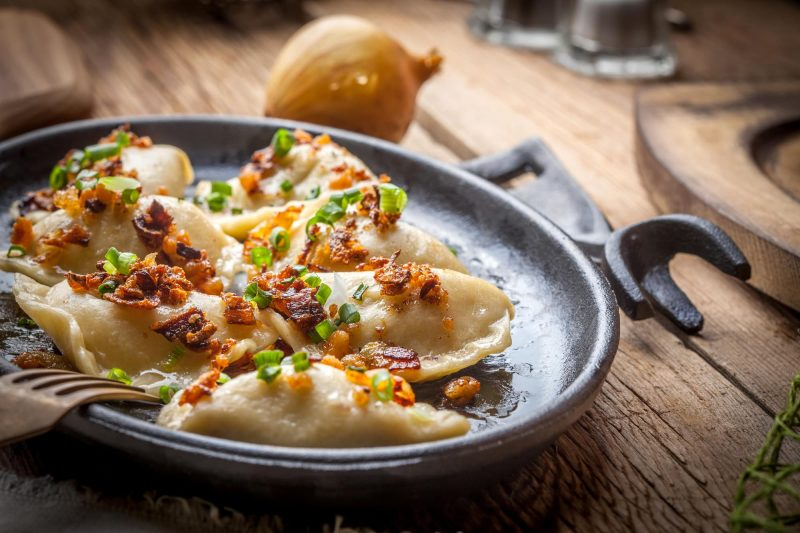 a metal skillet with Polish pierogies topped with scallions and bacon bits