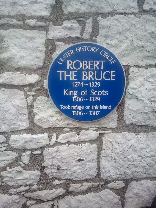 a blue historic plaque stating that Robert the Bruce took refuge onRathlin Island