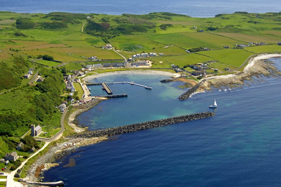 Rathlin Island harbour from a drone showing the pier and the small row of houses that are on the island