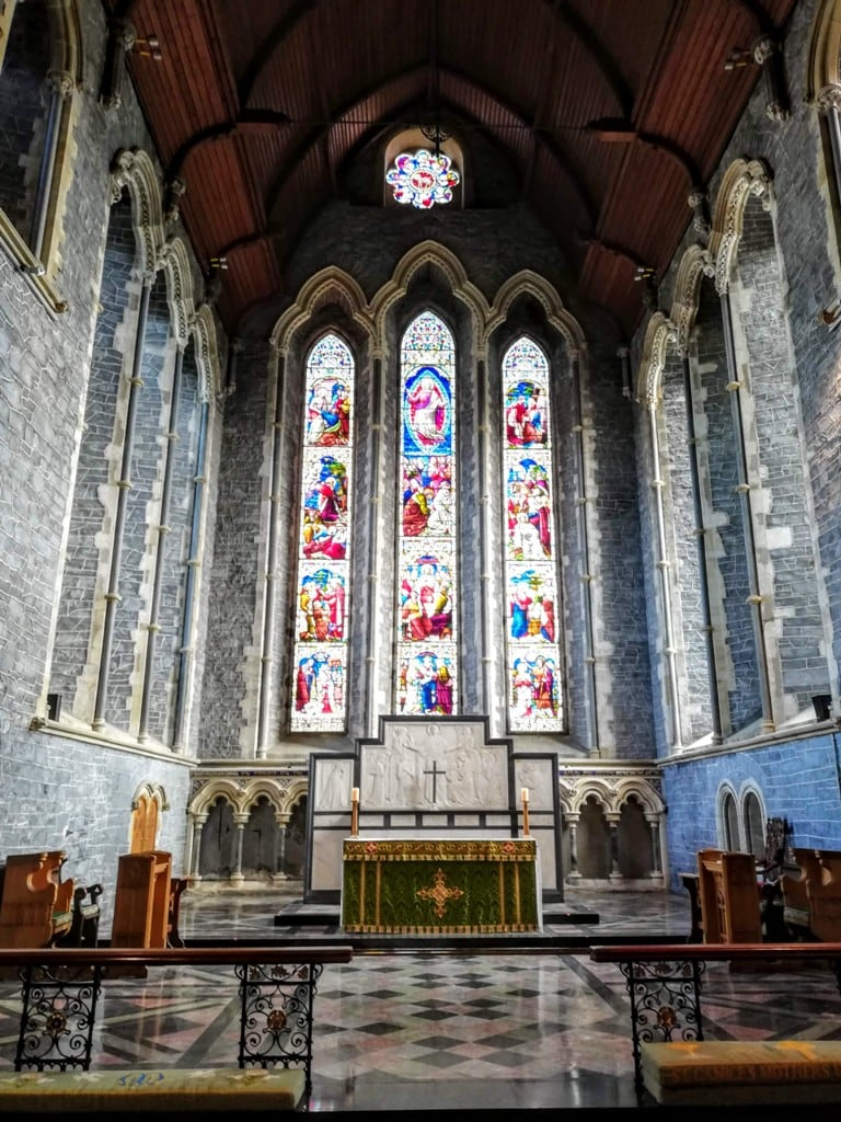 interior of St. Canice's Cathedral with the stained glass windows and rose window above the altar.