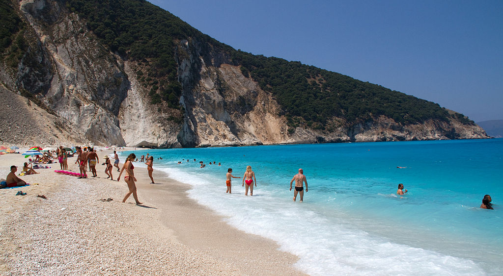 Underrated Destinations in Europe people on a gorgeous beach in Kefalonia called Mytros the beach sits at the feet of two mountains with pink sand that glows from the marble that washes up on the shores