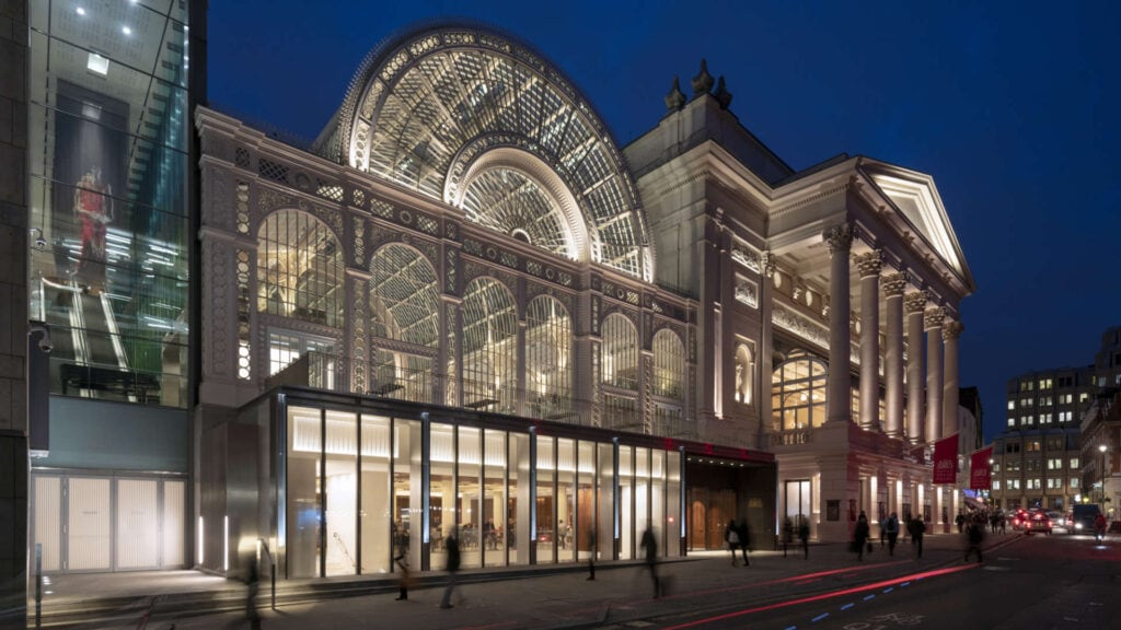 The Royal Opera and Royal Ballet company building at the Covent Garden Market slit up at night so you  can see the spectacular Victorian glass works