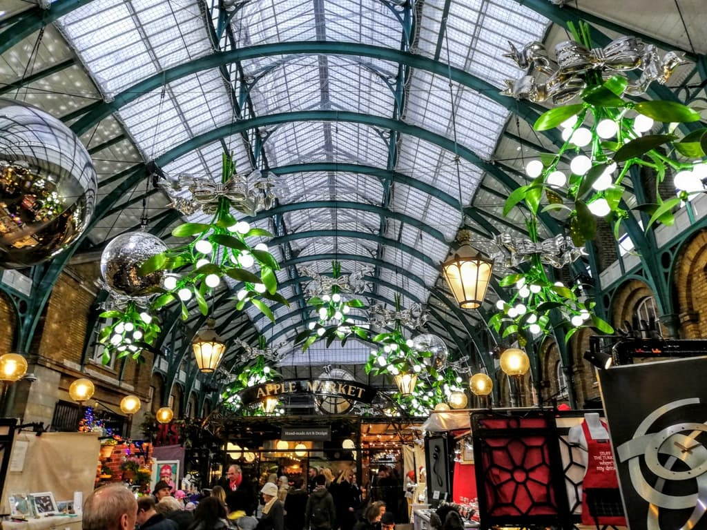 The Apple Market at Covent Garden market with its glass domed roof and large hanging Christmas decorations