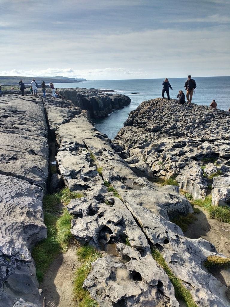 Tourists standing at the edge of the moonscape known as the Burren in Ireland