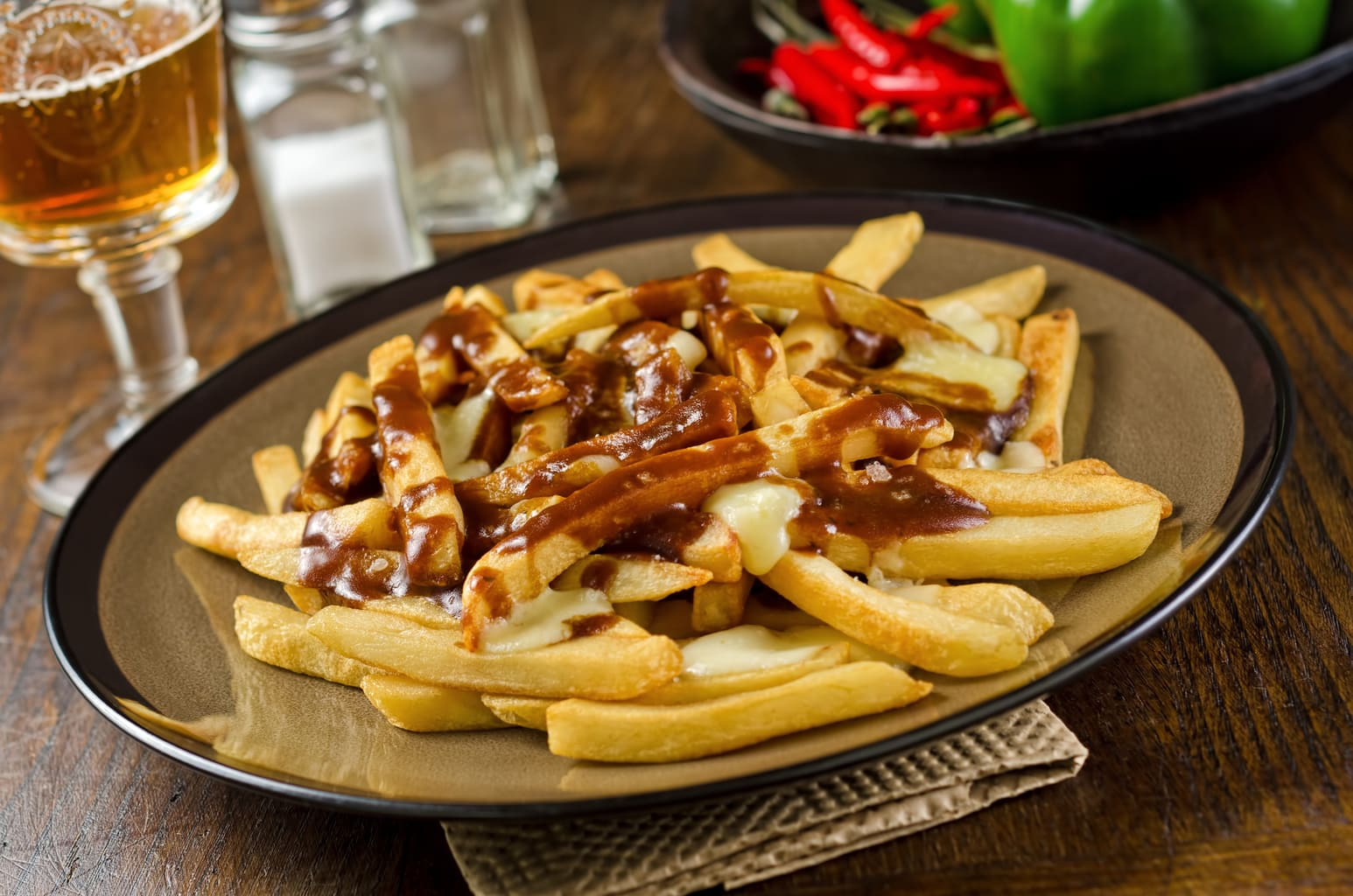 A plate of delicious poutine with french fries, gravy, and cheese curd.