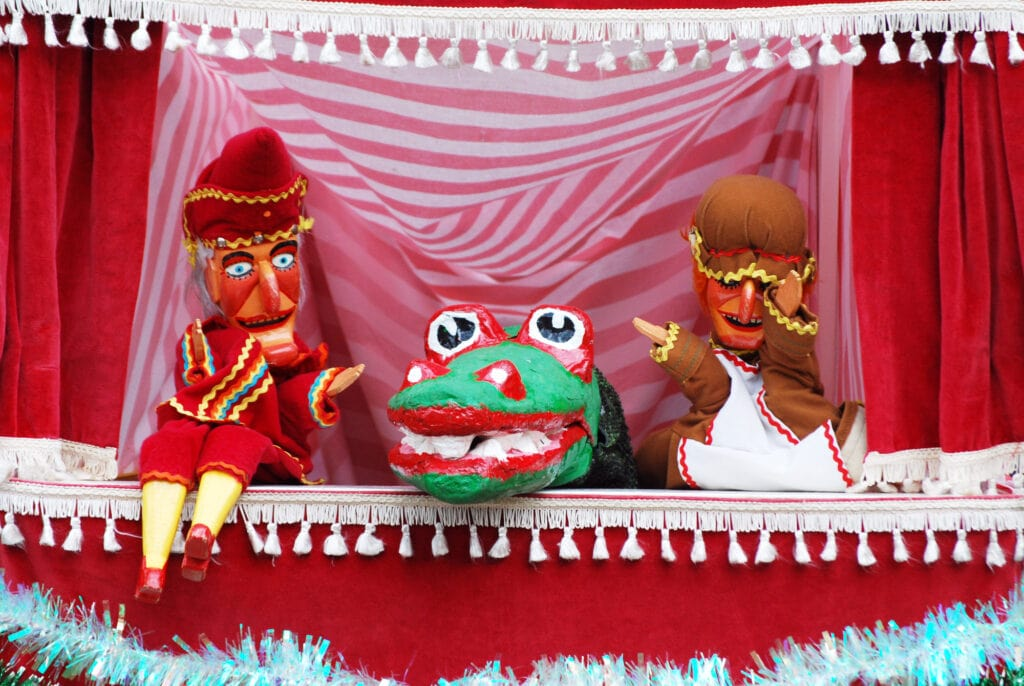 a Punch and Judy show at Covent Garden Market, set in a small red and white curtained booth with both Punch and Judy and the Dragon